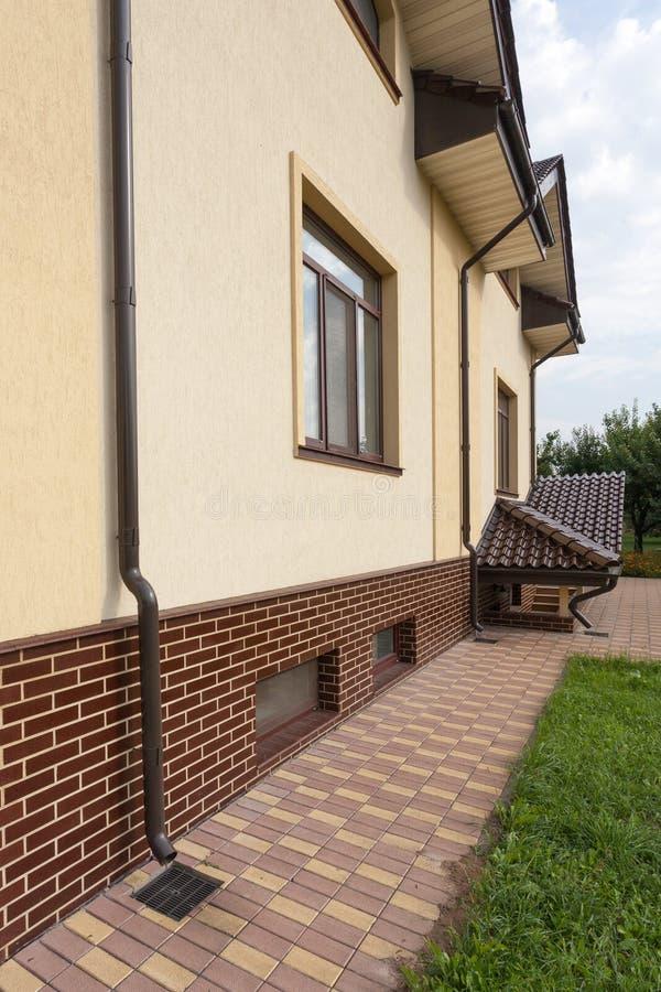 新的棕色铜天沟在有白色墙壁和新的砖的房子里 关闭在房子问题范围的看法雨天沟的 免版税图库摄影