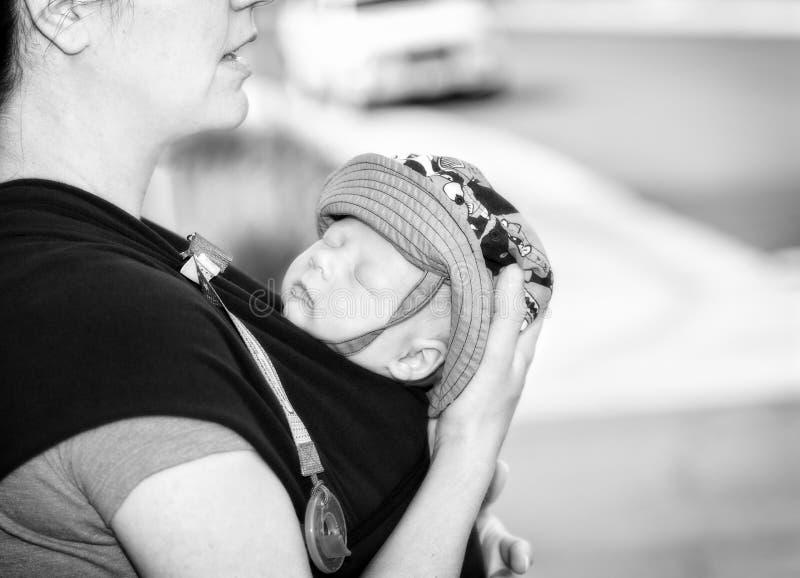 新的母亲拿着胸口载体的新出生的儿子 安慰者& Sunhat 免版税图库摄影
