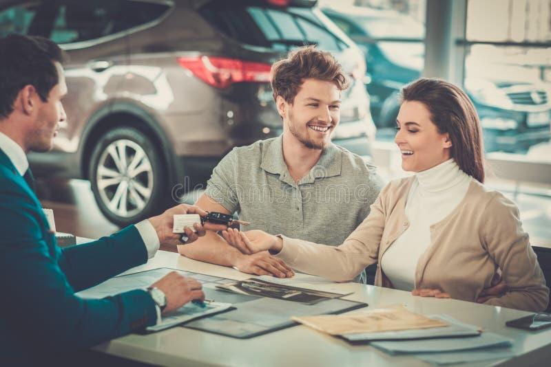 给新的汽车的钥匙的推销员一对年轻夫妇在经销权陈列室 免版税库存照片