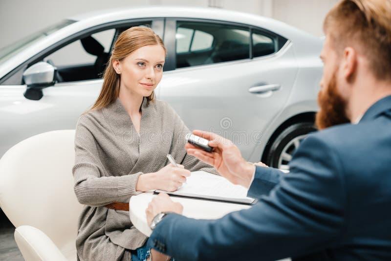 给新的汽车钥匙的有胡子的推销员少妇 免版税库存照片