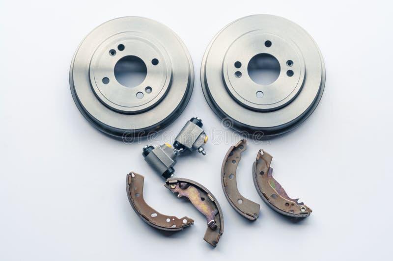 新的汽车零件刹车鼓,垫,在白色背景的圆筒 图库摄影