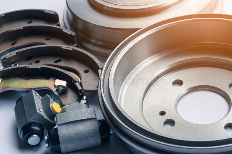 新的汽车零件刹车鼓,垫,在白色背景的圆筒 免版税库存照片