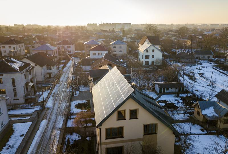 新的现代二层楼的房子村庄鸟瞰图与蓝色发光的太阳照片流电盘区系统的在屋顶 可更新 库存照片