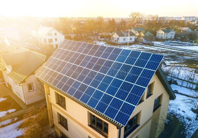 新的现代住宅二层楼的房子村庄空中顶视图与蓝色发光的太阳照片流电盘区系统的在屋顶 免版税图库摄影
