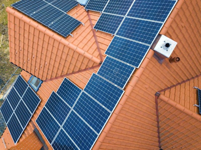 新的现代住宅房子村庄空中顶视图与蓝色发光的太阳照片流电盘区系统的在屋顶 可更新 免版税库存照片