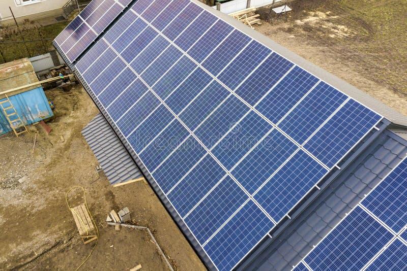 新的现代住宅房子村庄空中顶视图与蓝色发光的太阳照片流电盘区系统的在屋顶 可更新 免版税图库摄影