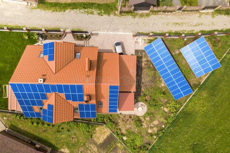 新的现代住宅房子村庄空中顶视图与蓝色发光的太阳照片流电盘区系统的在屋顶 可更新 库存照片