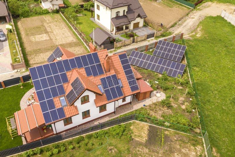 新的现代住宅房子村庄空中顶视图与蓝色发光的太阳照片流电盘区系统的在屋顶 可更新 库存图片