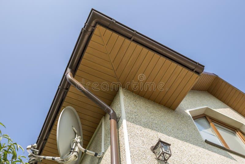 新的现代房子上面底视图细节与装饰灯和卫星盘在灰泥墙壁,塑料顶楼窗口,天沟p的 免版税图库摄影