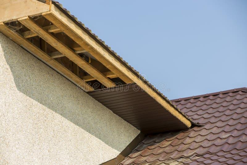 新的现代房子村庄角落底视图细节与灰泥墙壁、棕色盖的屋顶和未完成的支持的设施的  免版税库存图片