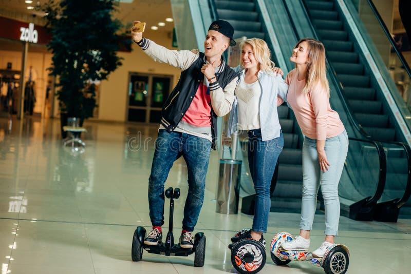 新的现代技术 做selfie的hoverboard的三个人 免版税图库摄影