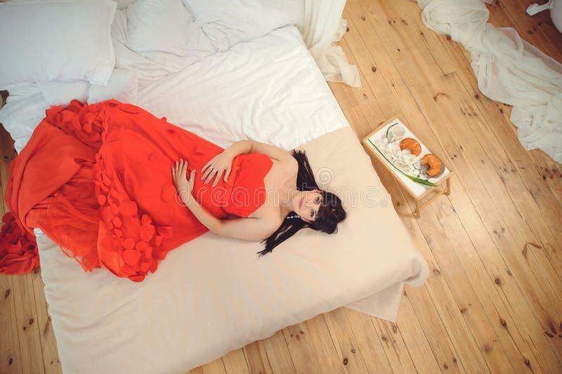 新的生命概念 怀孕、母性和幸福 孕妇特写镜头时髦的典雅的红色礼服的在床顶视图 免版税图库摄影
