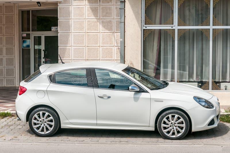 新的白色阿尔法・罗密欧Giulietta汽车在街道上停放了 库存图片