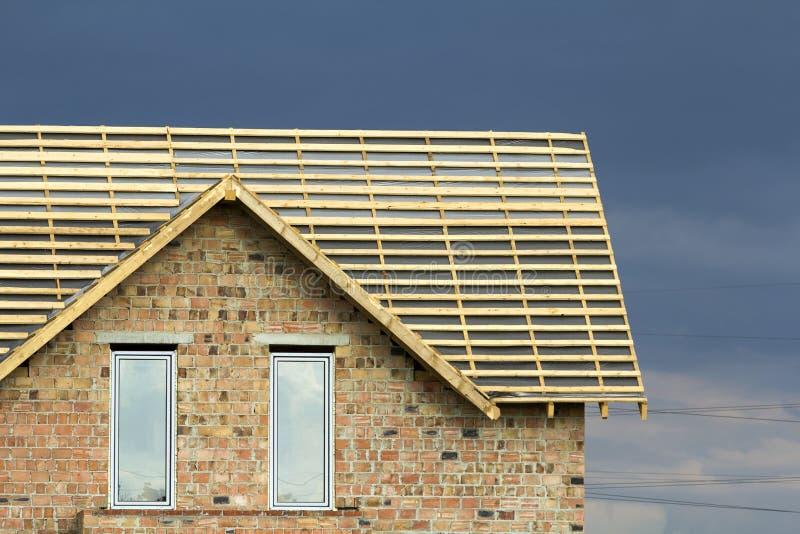 新的砖房子上面特写镜头细节与两个狭窄的塑料顶楼窗口的和木屋顶在深蓝构筑建设中 免版税库存照片