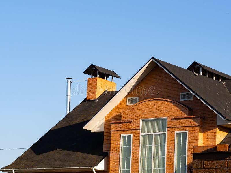 新的砖房子外部有长方形窗口和烟囱的在多重屋顶 免版税库存图片