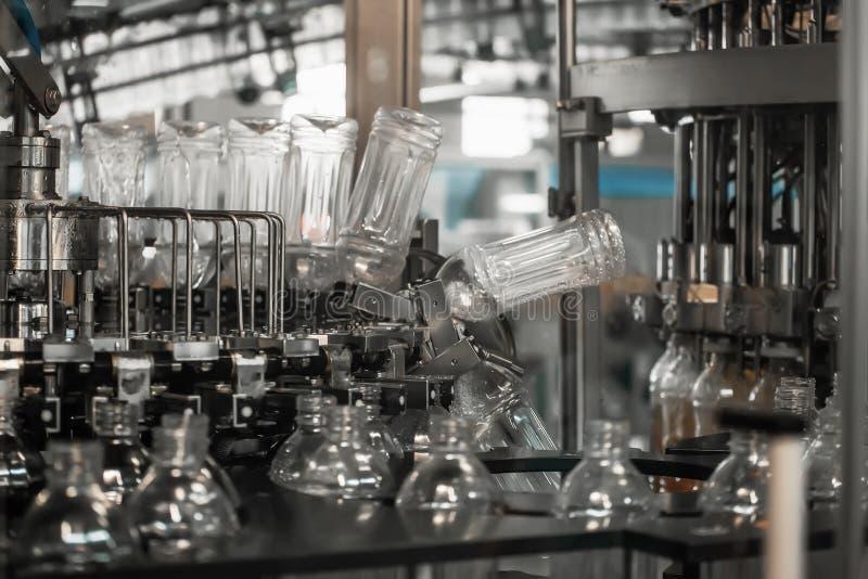 新的空的干净的在工业机器传动机线或传送带里面的宠物塑料瓶为填装用饮料做准备 免版税库存照片