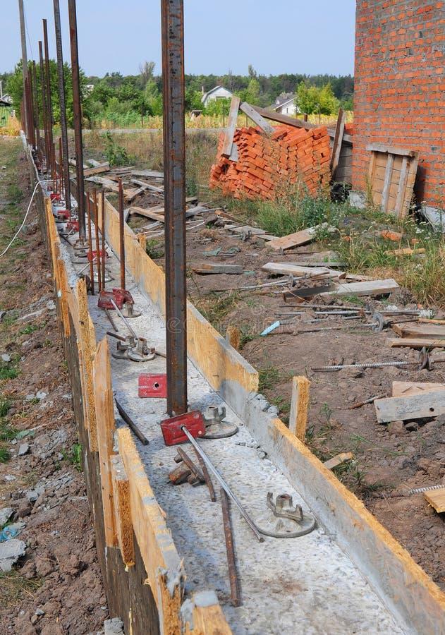 新的篱芭的修造的具体基础有金属支持 免版税库存照片