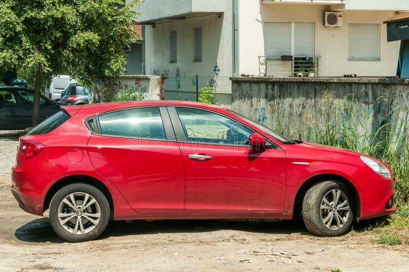 新的红色阿尔法・罗密欧Giulietta汽车在街道上停放了 库存图片