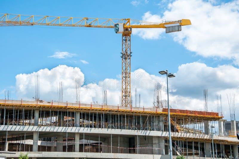 新的购物中心或购物中心建造场所在有起重机的机械,脚手架城市,具体与钢增强 免版税库存图片