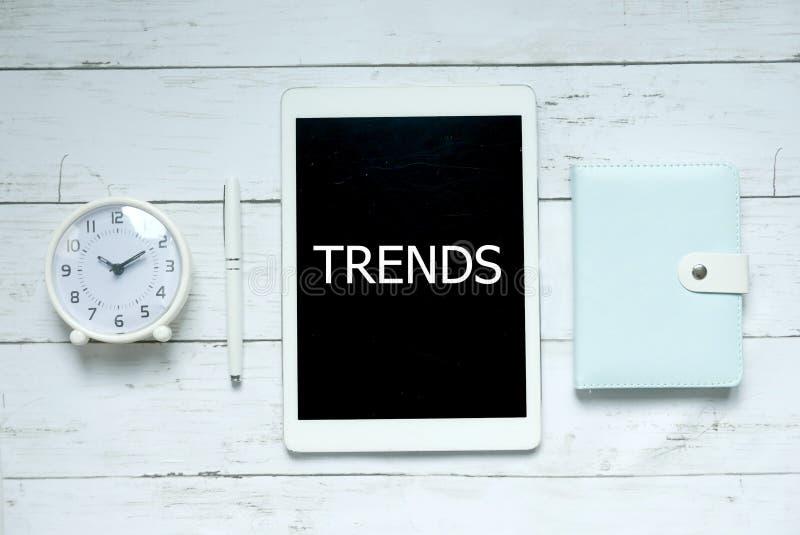 新的趋向技术企业概念 时钟、笔、笔记本和片剂顶视图写与趋向在白色木背景 库存图片