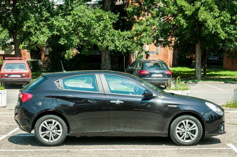 新的黑阿尔法・罗密欧Giulietta汽车在街道上停放了 图库摄影