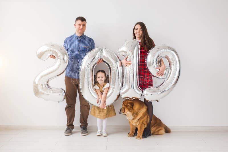 新的2019年是以后的概念-与狗的家庭在whithe屋子里举行银色色的数字 库存图片
