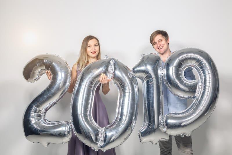 新的2019年是以后的概念-愉快的年轻人和妇女举行在白色背景的银色色的数字 图库摄影