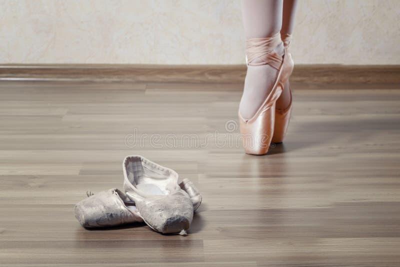 新的Pointe跳舞的芭蕾舞女演员在老和被撕毁的Pointe附近 免版税图库摄影