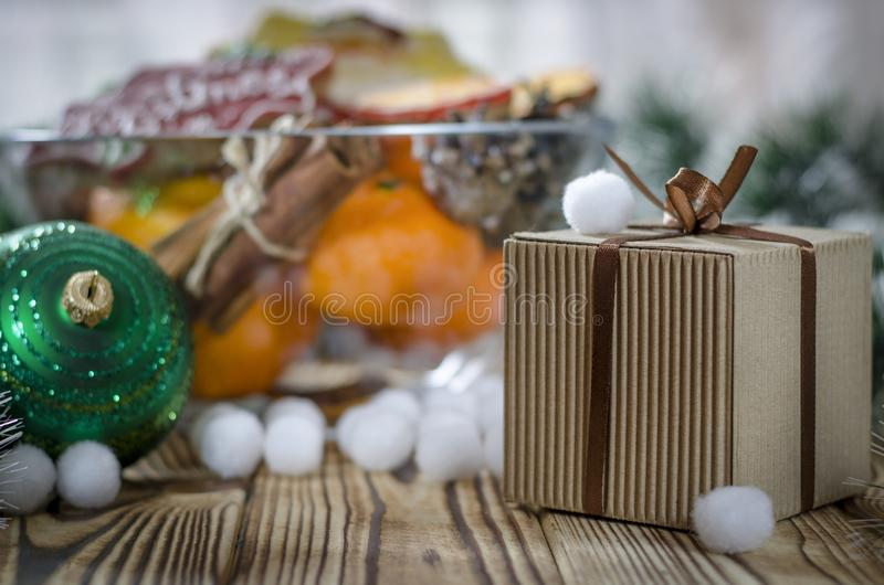 新的year';s礼物在木桌上站立在桔子、蜜桔、雪花和圣诞节玩具旁边 免版税库存图片