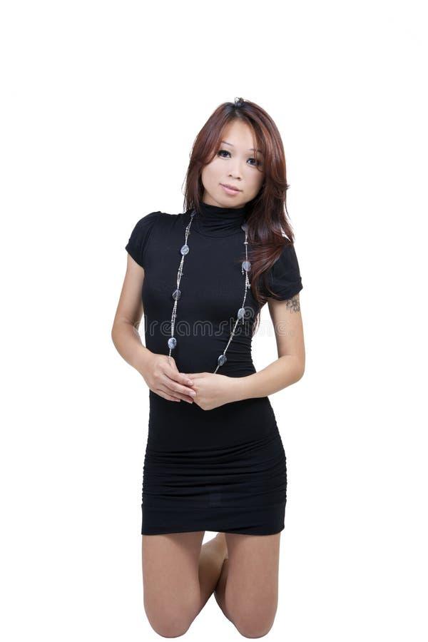 新皮包骨头的有吸引力的亚洲妇女黑色礼服 库存照片