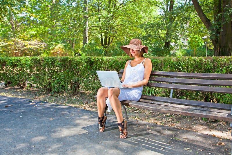 新端庄的妇女在公园和研究膝上型计算机 免版税库存图片