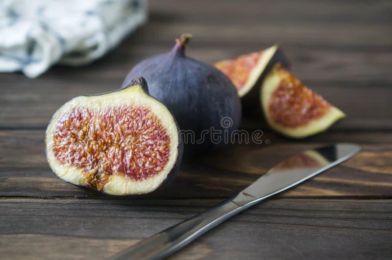 新紫色无花果果子和切片在木背景 免版税库存图片