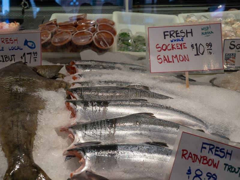 新红鲑鱼,虹鳟和大比目鱼和销售标志和价格在冰在鱼市商店前面 免版税图库摄影