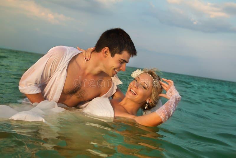 新结婚的夫妇游泳在海运 免版税库存照片