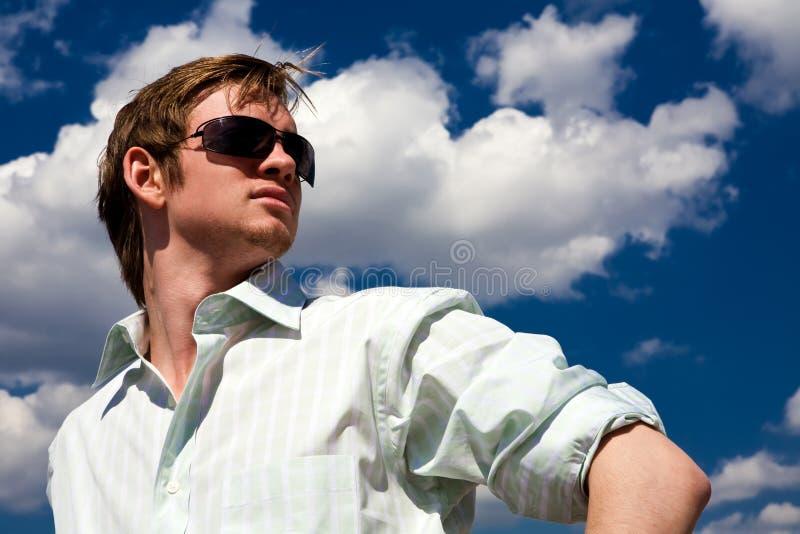 新蓝色人天空的太阳镜 免版税库存图片