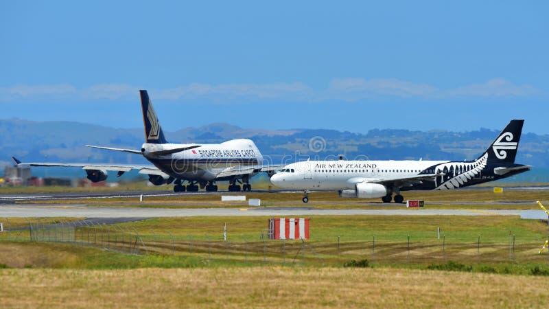 新西兰航空公司乘出租车的空中客车A320,当新航波音747-400货轮在奥克兰国际机场时离开 库存图片
