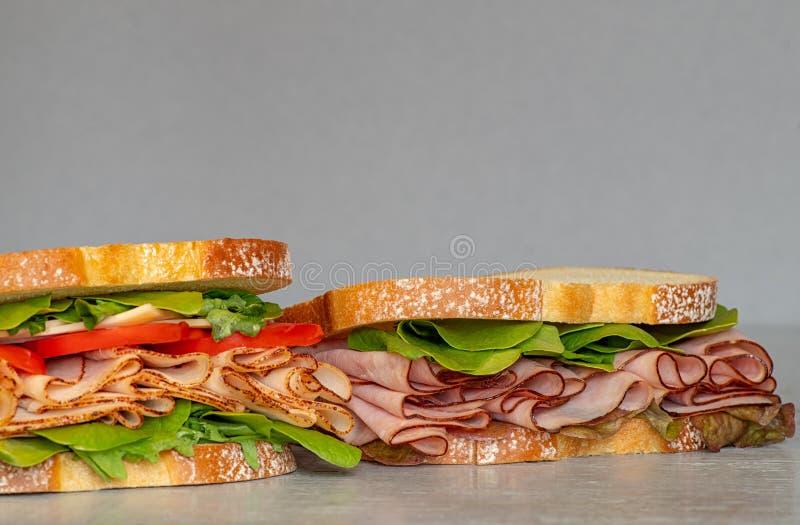 新近地做了熟食店样式三明治用莴苣,菜,蕃茄,乳酪,肉几不同形式相似与火腿, 免版税库存图片