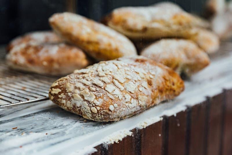 新近地和温暖顶面大理石柜台的被烘烤的小圆面包地方出售的 自创由工匠 免版税库存图片