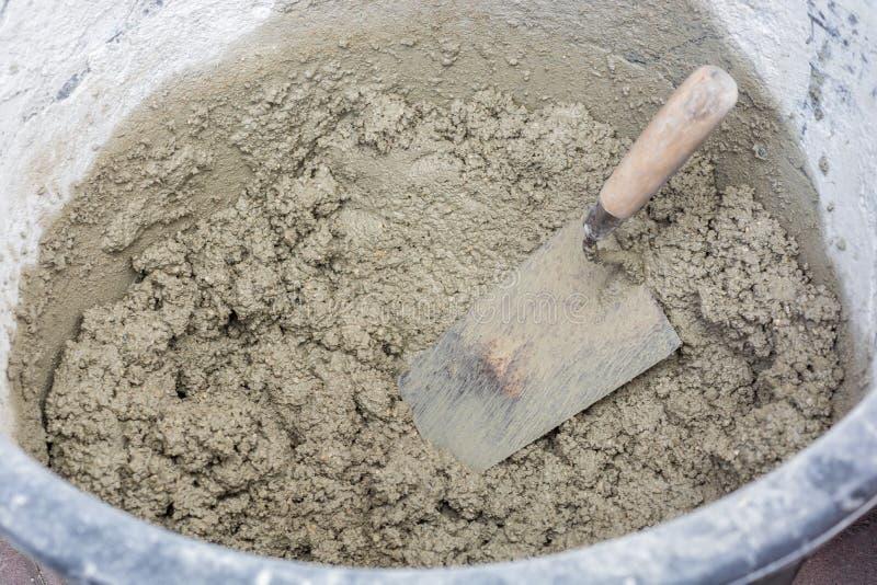 新近地接触了在灰浆桶的冗长的句子有修平刀的 免版税库存照片