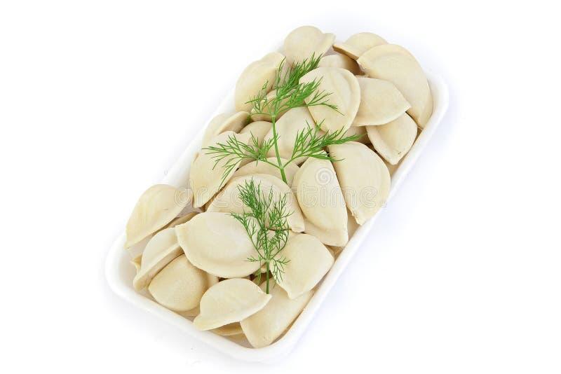 新近地结冰的半成品 与您的饺子,土豆 产品在塑料potdtons被包装 在白色的孤立 库存照片