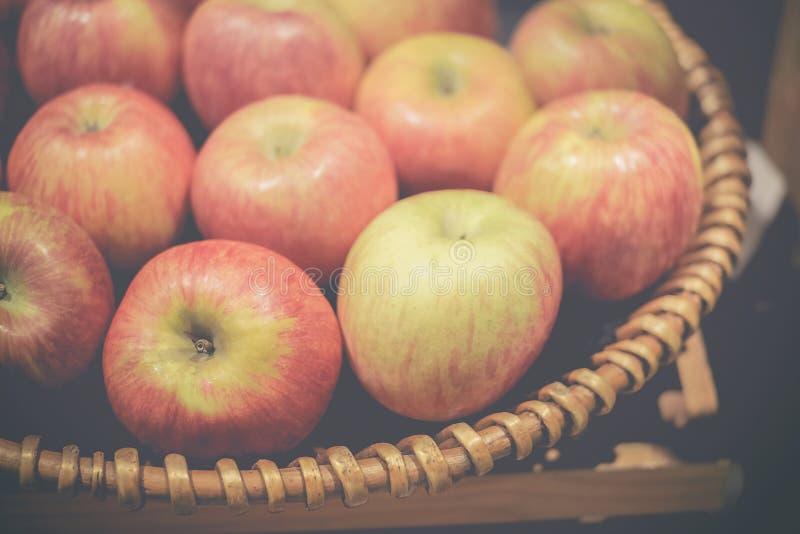 新近地色的苹果在藤条篮子 图库摄影
