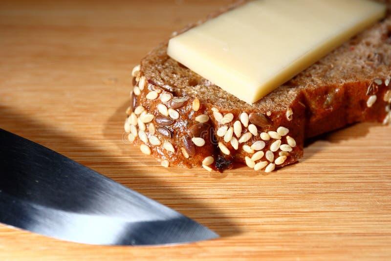 新近地被烘烤的多五谷面包用在木背景的乳酪 免版税库存图片