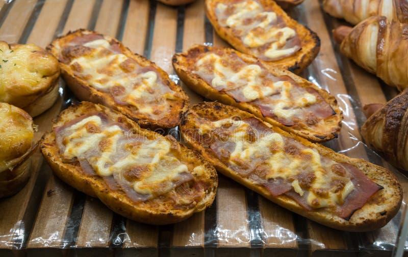 新近地被烘烤的火腿和乳酪与蛋黄酱酥脆面包切片 免版税图库摄影