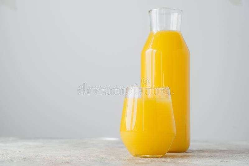 新近地被紧压的橙汁过去水平的射击由在玻璃容器的柑橘制成,隔绝在与空白的白色背景 免版税库存图片