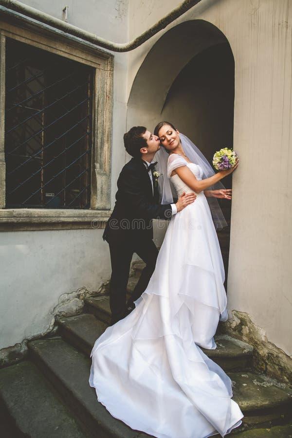 新郎亲吻弯曲她的新娘的面颊在入口 库存照片