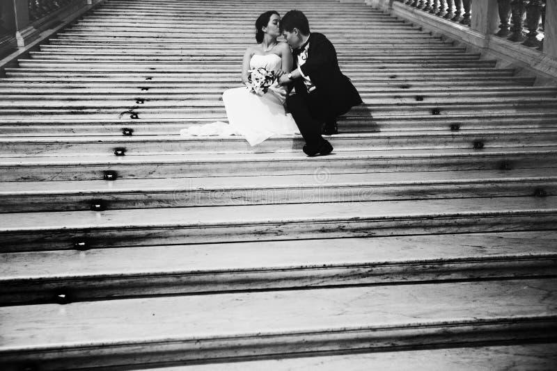 新郎亲吻新娘` s肩膀与她坐大理石sta 库存图片