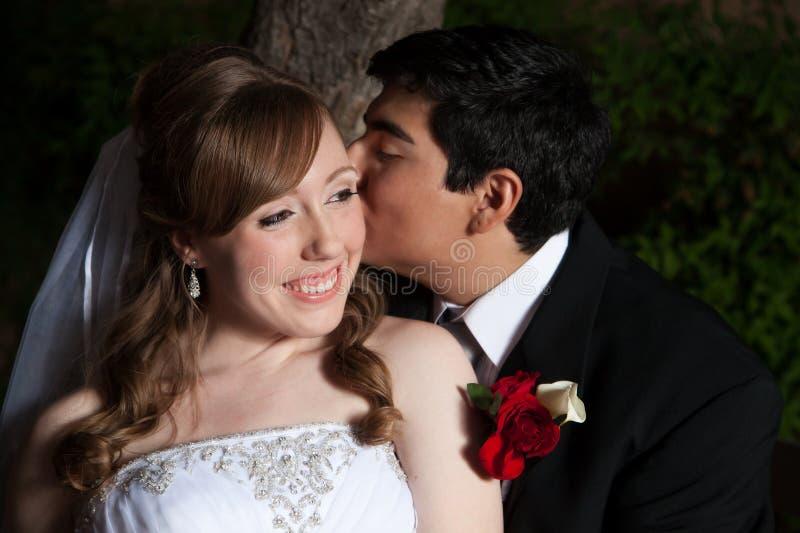 新郎亲吻面颊的新娘 库存图片