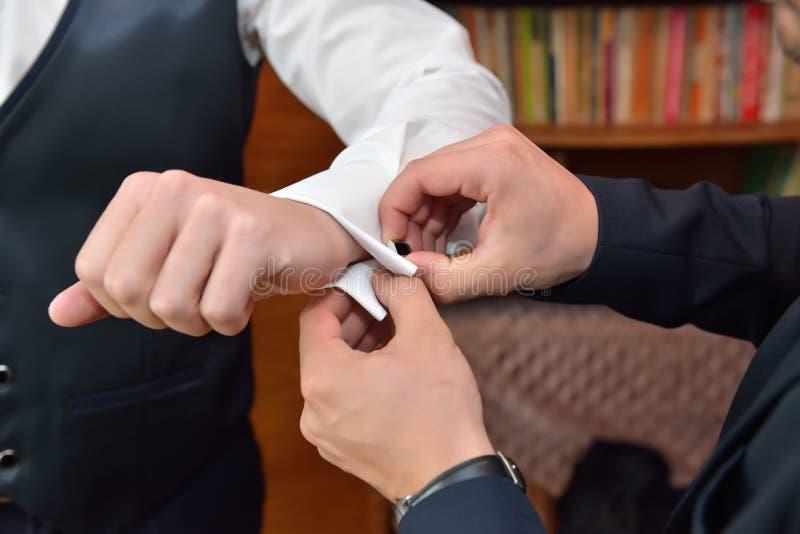 新郎人在白色sl帮助新郎投入黑链扣 库存图片