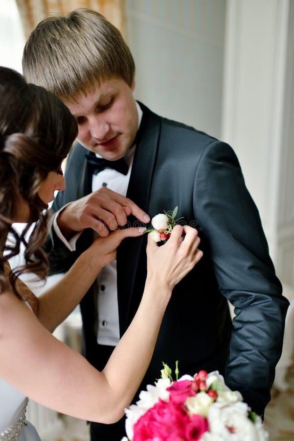 新郎和新娘佩带钮扣眼上插的花户内 免版税库存照片