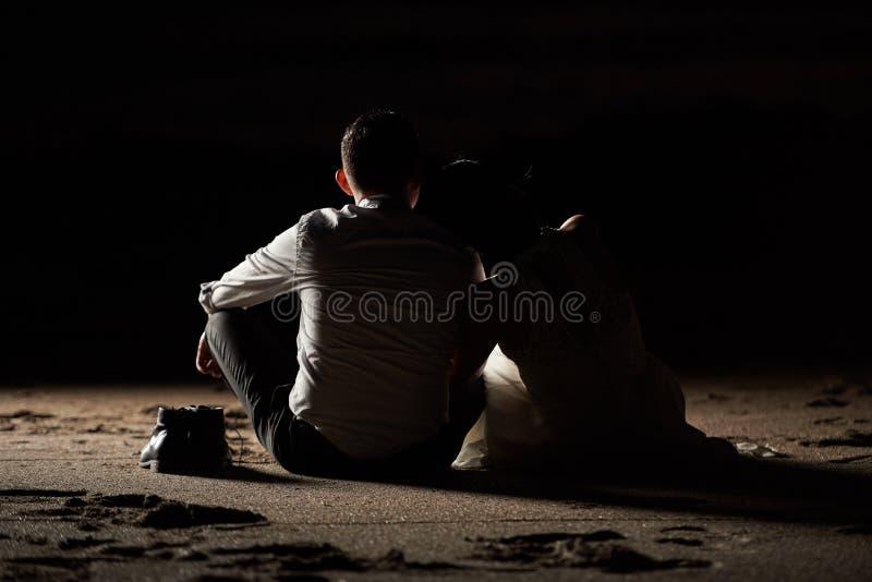 新郎和新娘坐海滩沙子 库存照片